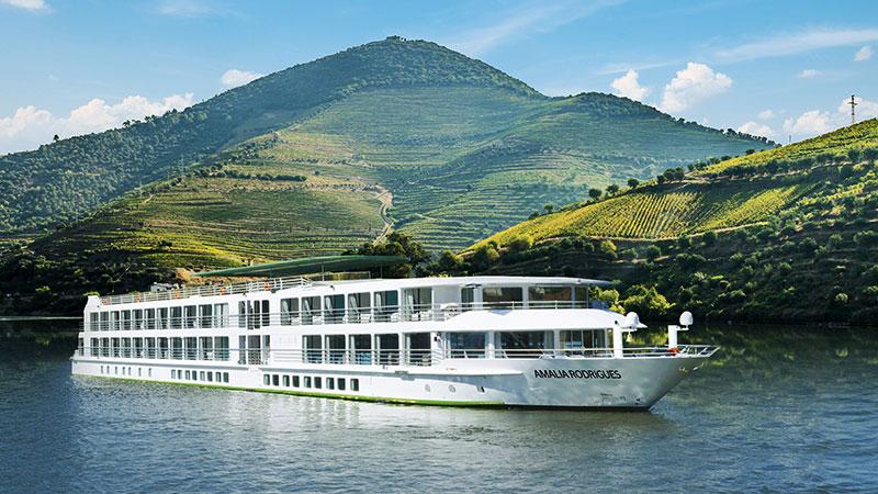 Stort elvecruiseskip seiler nedover elven Douro i frodig landskap.