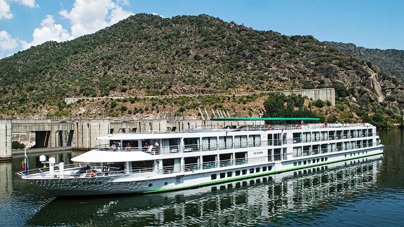 Elvecruiseskip ved kai på elven Douro. Grønt fjell i bakgrunnen.