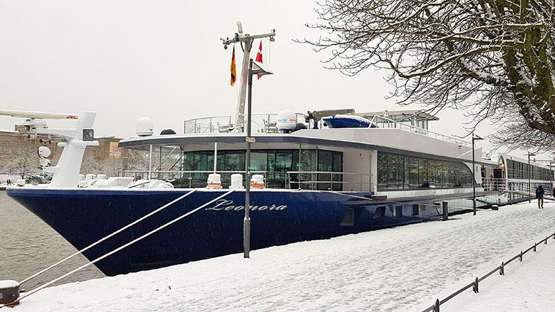 Elvecruisebåten MS Leonora ved kai på vinterstid. Promenade og trær med mye snø.