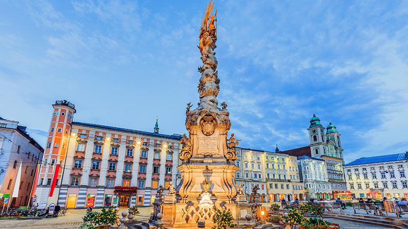 Stor statue opplyst foran en stor ærverdig bygning i sentrum av byen Linz
