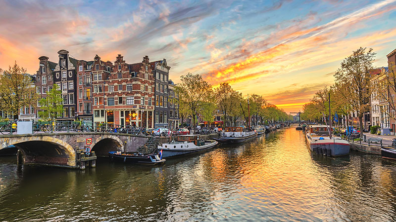 Amsterdam i solnedgang. Husbåter på en av kanalane gjennom byen.