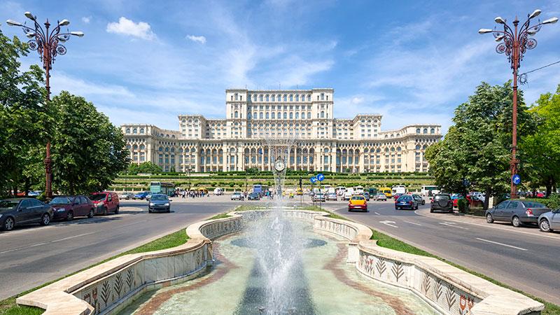 Et enorm palass i Bucuresti med en stor fontene i front. Flere biler på veien rundt fontenen.