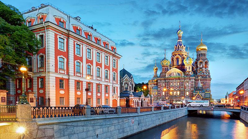 Fargerik kirke i St. Petersburg ved en kanal på kveldstid. Rødt bygning i fronten.