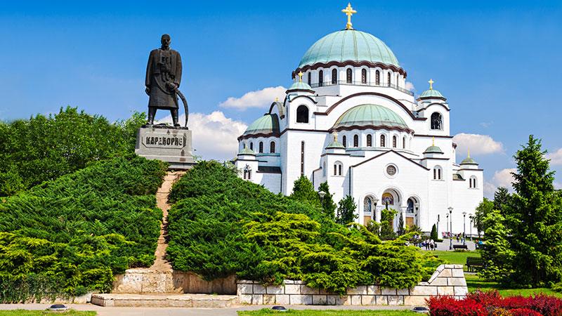En gammel kirke i byen Beograd med en stor statue ved siden av. Frodig park.