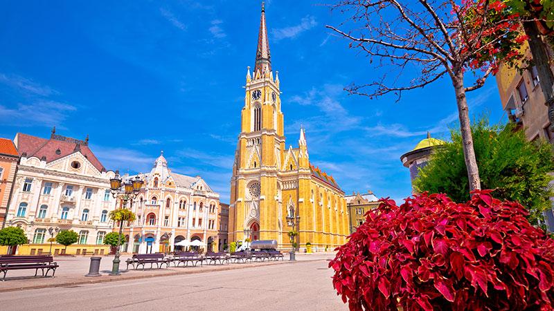 Stor kirke ved en åpen plass i Novi Sad. Trær og benker i ulike farger.