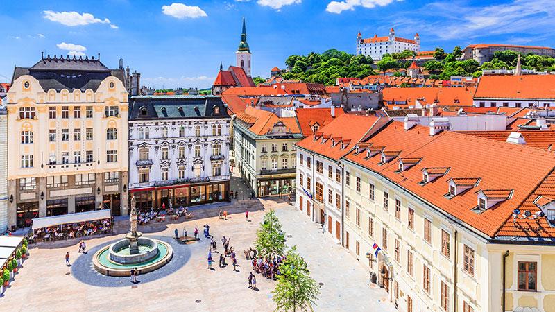 Gamle og ærverdige bygninger i sentrum av Bratislava. Stor plass med statue og mange mennesker.