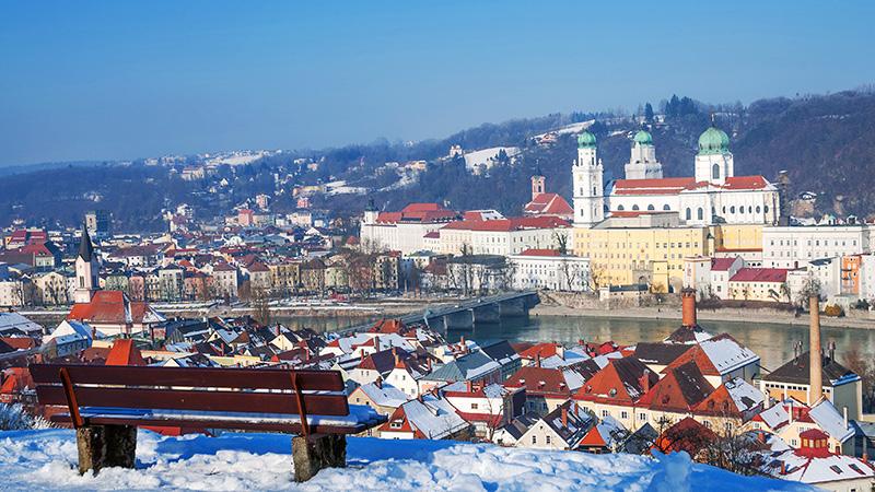 Den tyske byen Passau på vinterstid. En benk i en park med utsikt over byen.