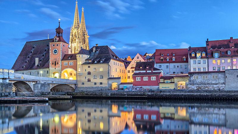 Utsikt fra Donau inn mot byen Regensburg. Opplyste kirkespir bak noen bygninger.