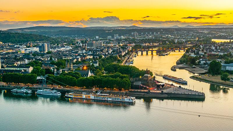 Møtepunktet der Mosel og Rhinen møtes. Flere elvecruisebåter ligger ved kai på kveldstid.