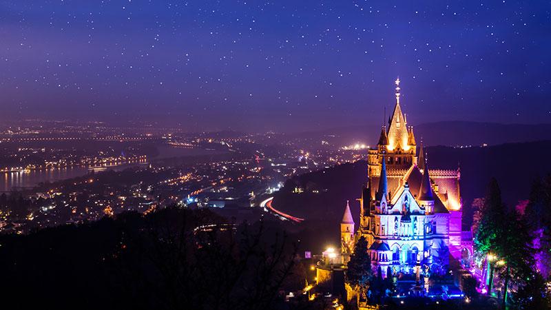 Et opplyst slott på kveldstid med utsikt over Königswinter.