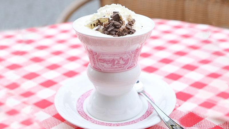 En kopp kaffe på bord med rutete duk.