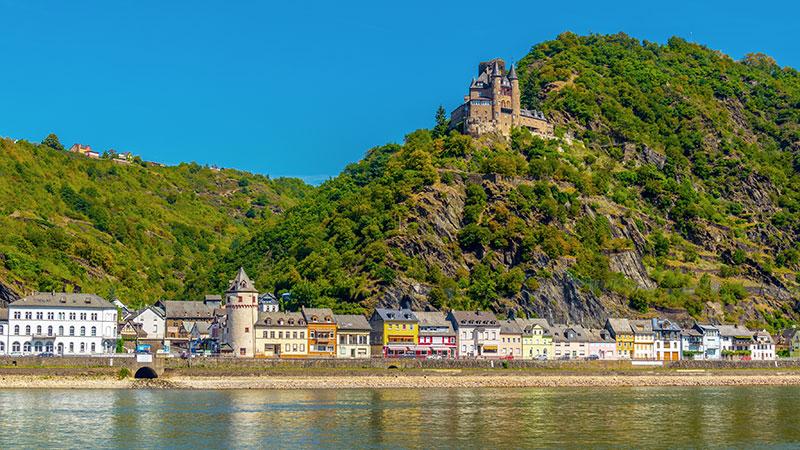 Utsikt fra Rhinen opp mot St. Goarhausen oppe på en ås. En liten landsby i fronten.