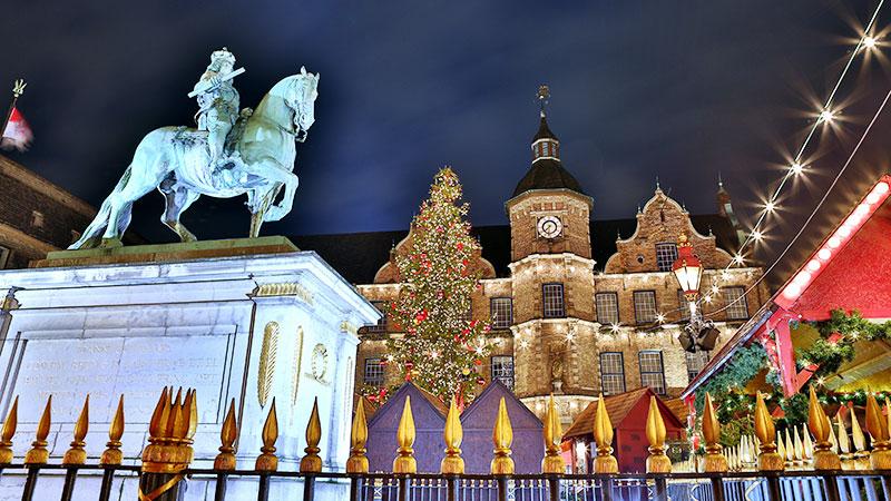Julemarked med juletre i Düsseldorf. En statue av en mann på hest.