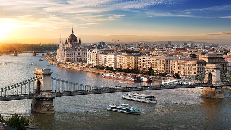 To elvecruise båter under stor bro i Budapest. Solnedgang over byen.