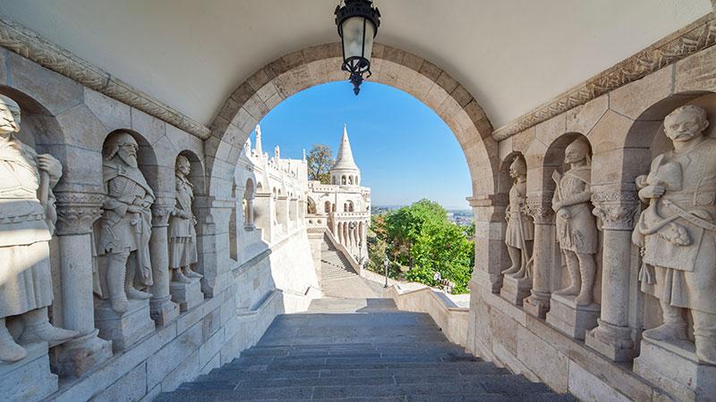 En liten tunnel ved en borg med gamle statuer på hver side.