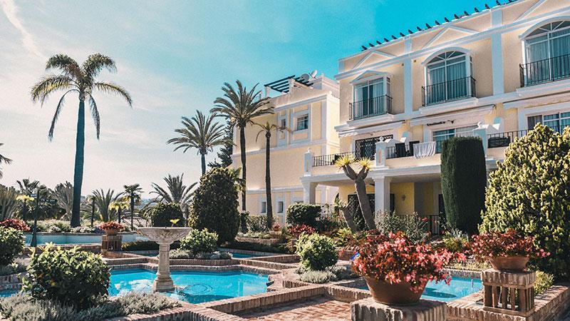 En hage med fontener, palmer og små pools foran leilighetene.