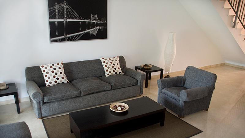 Sofa gruppe og bord i stue. Trapp i bakgrunnen.