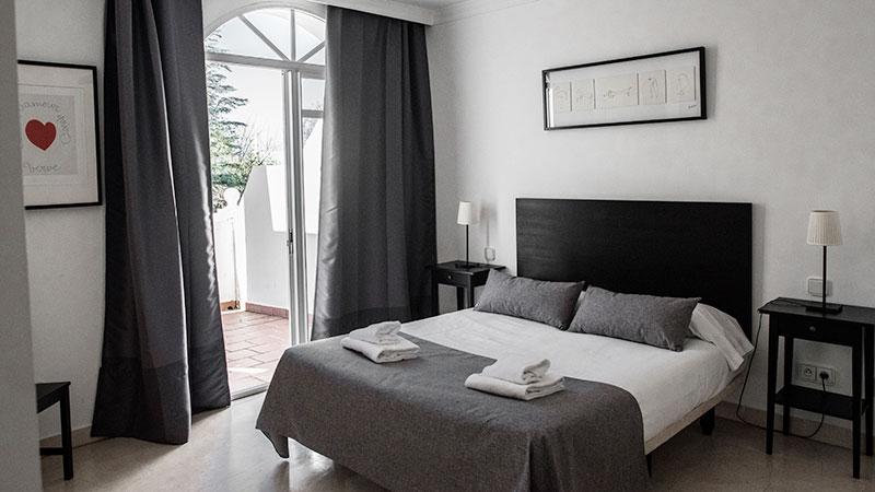 Dobbeltseng i soverom med utgang til terasse. Bilder på vegg og lampe på kommode.