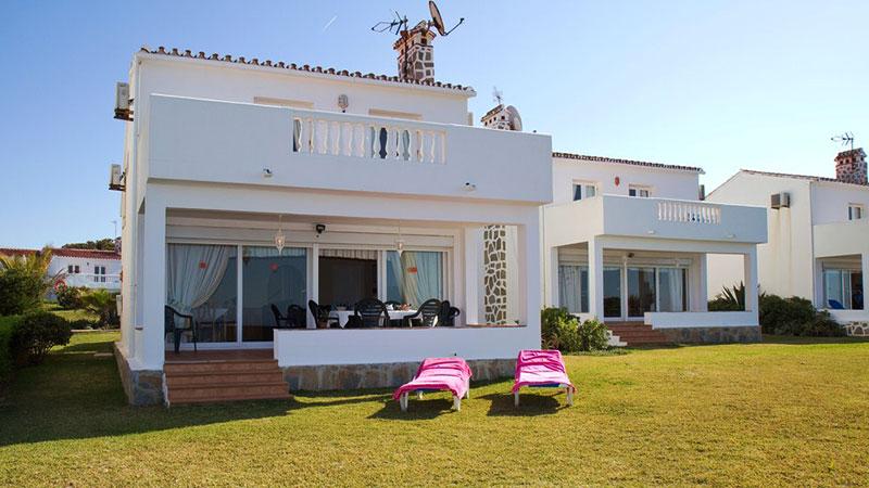 Stor villa ved stranden. En hage med solsenger og en terrasse.