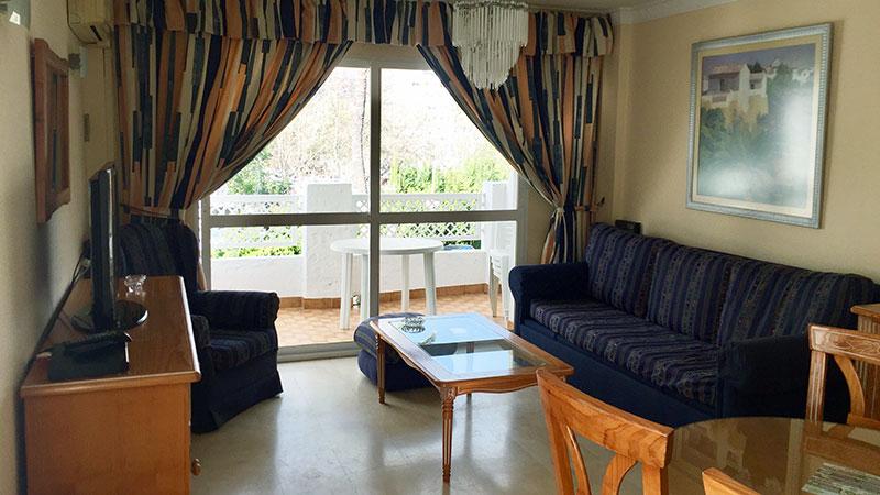 Stue i leilighet med bord, tv og spisebord. Utgang til terrasse.