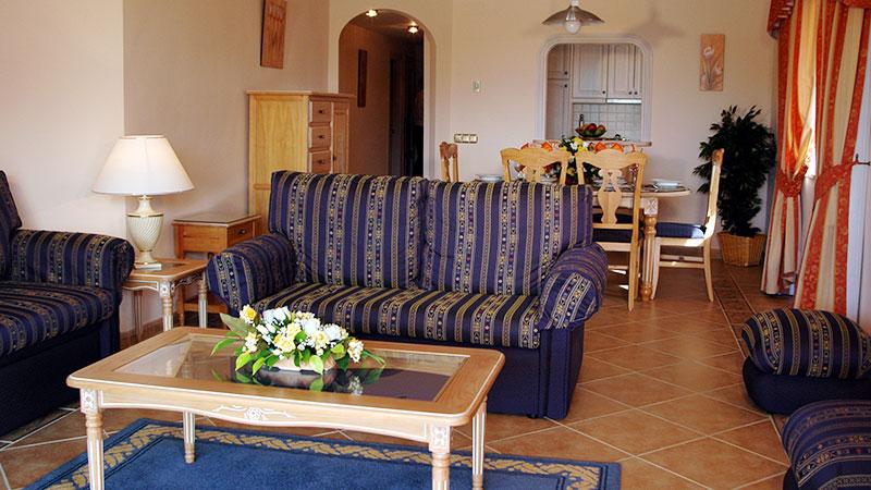Stue med sofagruppe, bord og spisebord. Innsyn til kjøkken.
