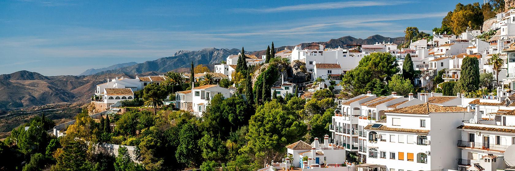 En hvit landsby oppe i fjellene på solkysten.