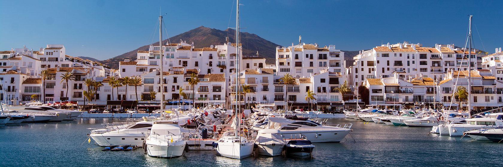 En båthavn med mange fritidsbåter. En by med mange hvite hus og et fjell i bakgrunnen.