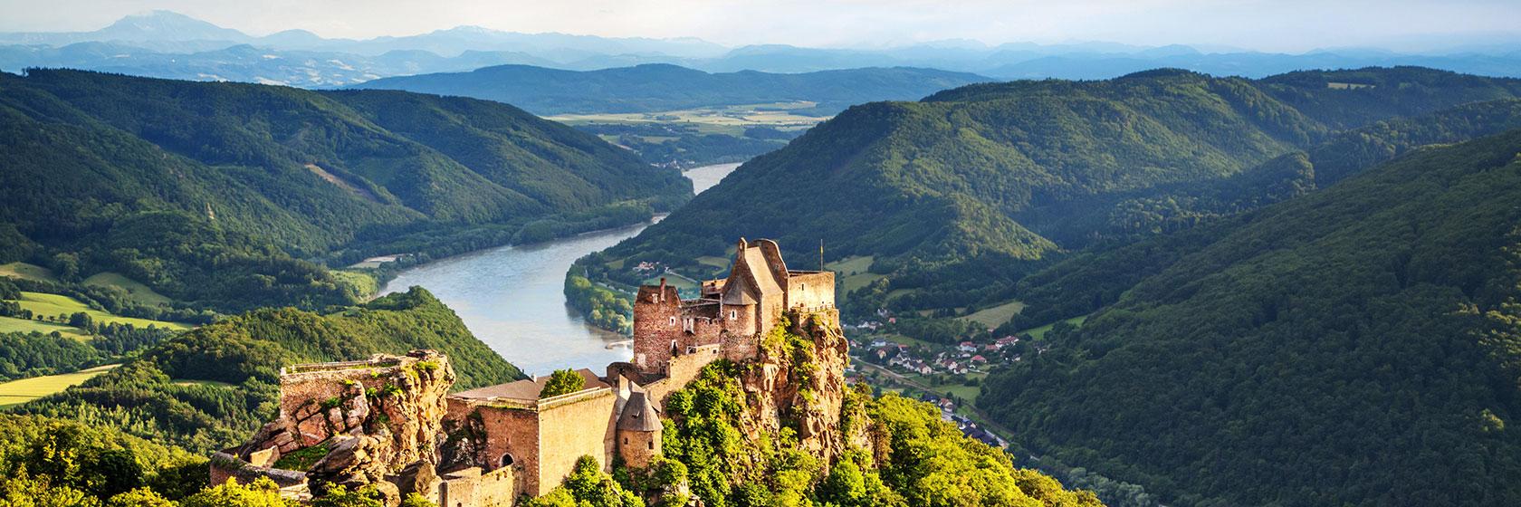 En elv som renner gjennom en vakker dal. Et stort slott har flott utsikt.